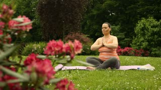 Pregnant woman looks calm while sitting on the mat in the garden and doing yoga
