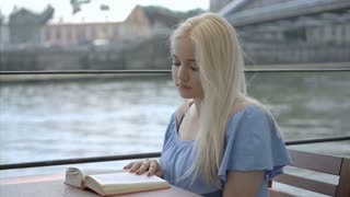 Pretty blonde girl sitting on the boat and reading book
