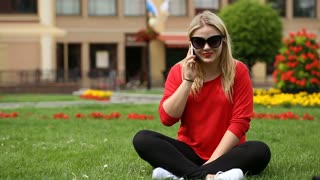 Pretty, blonde girl sitting on the grass and chatting on cellphone