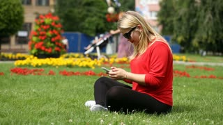 Pretty, blonde girl sitting on the grass and laughing while texting on smartphon