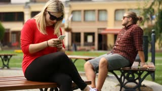 Pretty girl looks satisfied while sitting on the bench and texting on smartphone