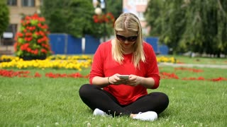 Pretty girl sitting on the grass in the park and texting on smartphone