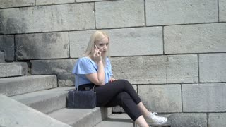 Pretty girl sitting on the stairs and looks angry while speaking on cellphone