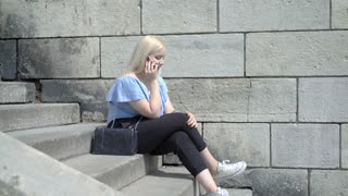 Pretty girl sitting on the stairs in the city and chatting on cellphone