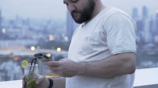 Relaxed man drinking alcoholic drink on the roof and browsing internet on smartphone