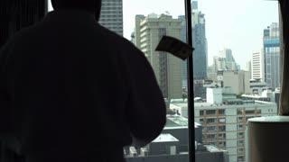 Rich man wearing bathrobe and throwing dollars, slow motion shot at 240fps