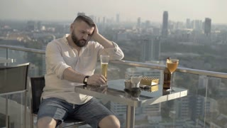 Sad man sitting in skybar and drinking beer