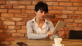Shocked attractive woman reading bad news on tablet computer sitting in cafe