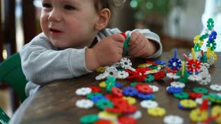 Small kid looks absorbed while playing with colorful blocks