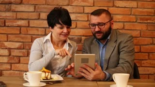 Smile couple watching tablet in cafe