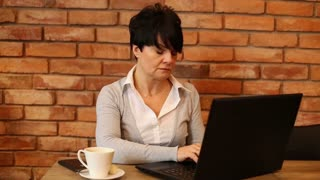 Tired attractive businesswoman with laptop in cafe