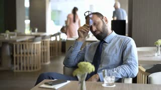 Tired businessman sitting in the cafe