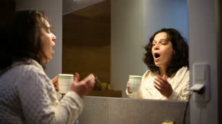 Tired woman yawning in the bathroom and drinking coffee