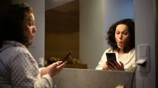 Tired woman yawning while speaking on cellphone in the bathroom