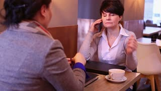 Two women sitting and talking on cellphone  in cafe
