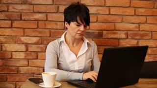 Unhappy, angry woman with  laptop in cafe