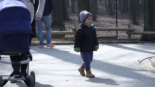 Upset boy walking in the zoological garden, slow motion shot at 240fps