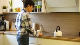 Woman boils the water and making coffee while standing in the kitchen