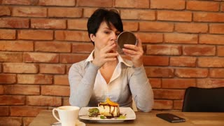 Woman checking sking on her face sitting in cafe