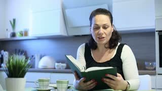 Woman sitting in the kitchen and reading book out loud