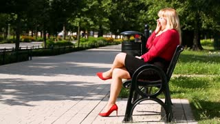 Woman sitting in the park and yawning
