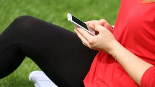 Woman sitting on the grass and texting on smartphone