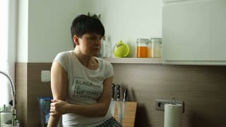 Woman sitting on worktop in the kitchen and talking to someone