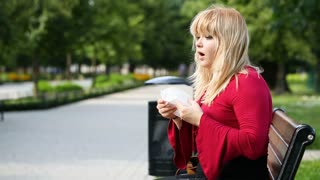 Woman sneezing in the park and looks poor