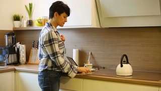 Woman standing in the kitchen and pouring boiling water to the cup