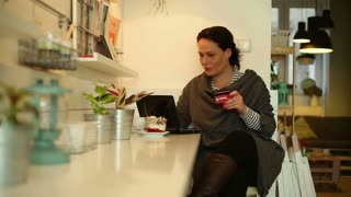 Woman using laptop for online shopping in cafe