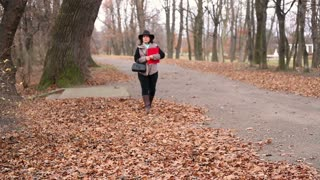 Woman with documents, walking in the autumnal park