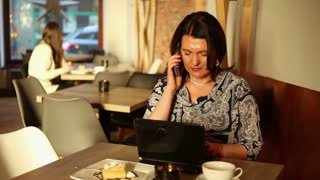 Woman working on laptop talk cellphone and sit in cafe