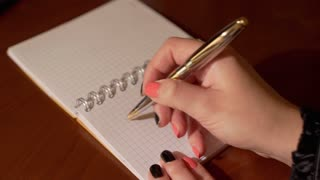 Woman's hand writes word STOP on the notebook