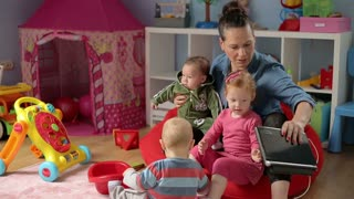 Women play with her children in a playroom