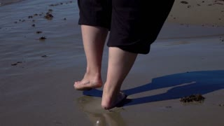 Womens feets walking on beach, super slow motion