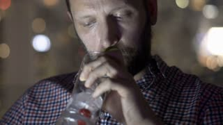 Worried man drinking alcohol at night and thinking about his problems