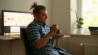 Worried man sitting in the office at home and eating cake