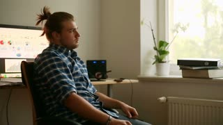 Worried man sitting in the office at home and looking to the camera