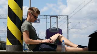 Young man finish using laptop while sitting on platform and relaxing