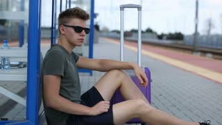 Young man looks calm while sitting on the platform and waiting for his train