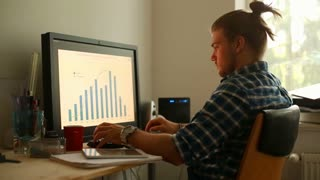Young man sitting in the home office and working on computer