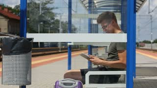 Young man using tablet on the train stop while waiting for the arrival