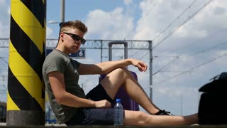 Young man waiting for train on platform and looks thoughtful