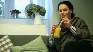 Young woman drinking orange juice in cafe