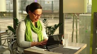 Woman closing laptop and looking at the camera