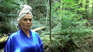 Woman in a bathrobe is smiling to camera in the forest