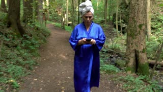 Woman in a bathrobe is walking at the forest and writing sms