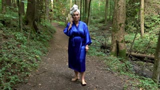 Woman in a bathrobe is walking in forest and talking for cellphone