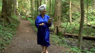 Woman in a bathrobe with tablet is walking at the forest