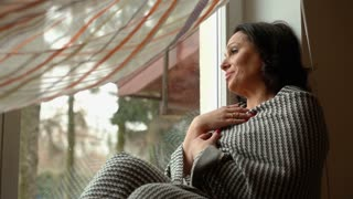 Woman yawns, sitting on windowsill wrapped in a blanket